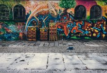 A wall with spray paint graffiti on