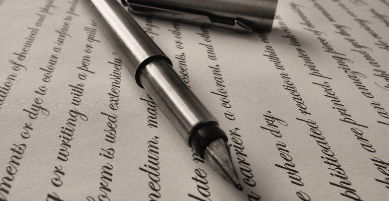 A silver pen on top of calligraphy writing