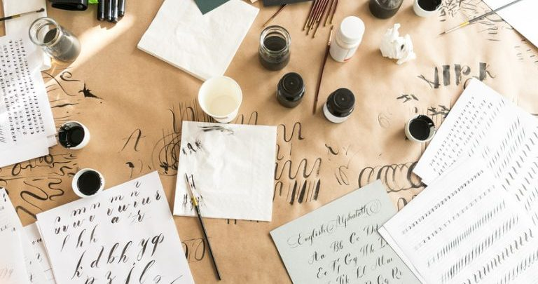 Calligraphy pens and ink with a wriitng pad with calligraphy letters on
