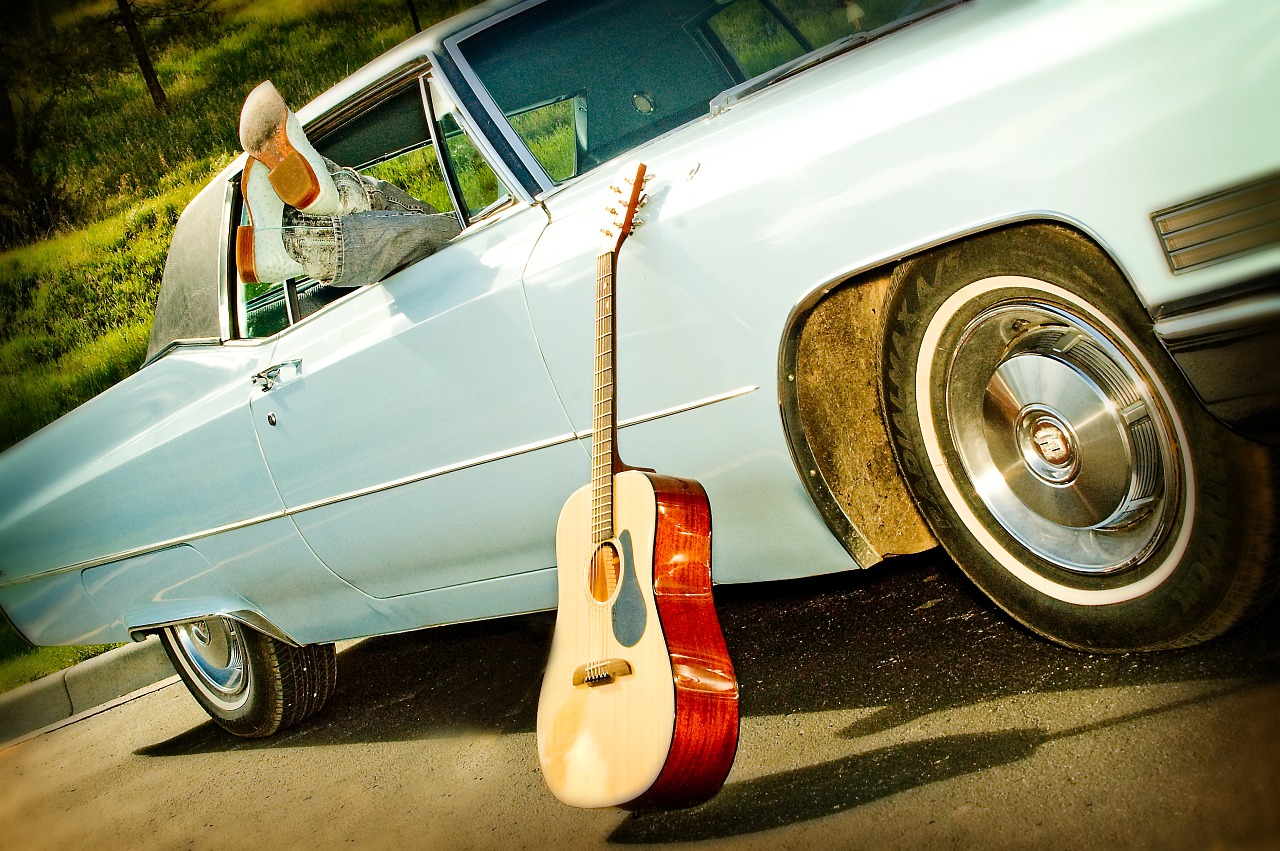A guitar leaning against an old car