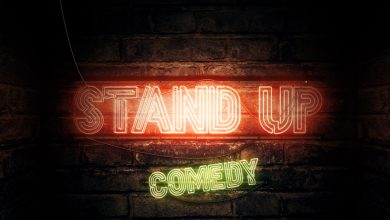 """A neon sign on a wall that reads """"stand up comedy"""""""