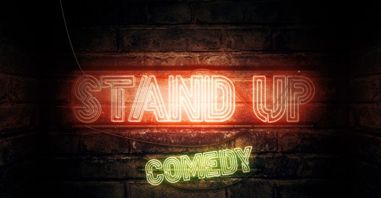 "A neon sign on a wall that reads ""stand up comedy"""