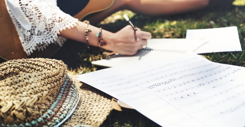 A girl with a guitar writing a song