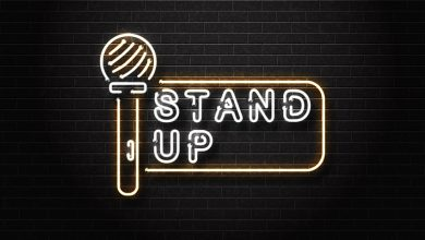 The word stand up and a microphone illuminated on a brick wall