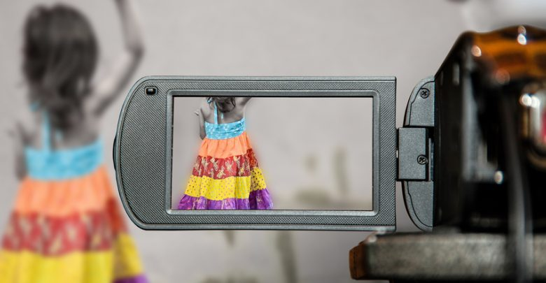 A girl in a colorful dress being filmed by a prosumer camcorder
