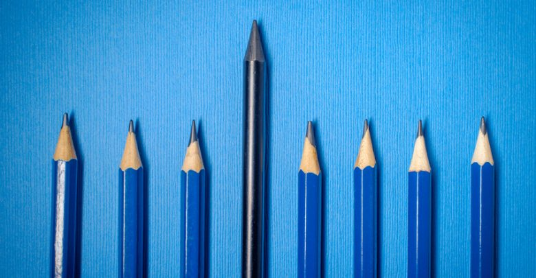 Row of artist graphite pencils on blue background