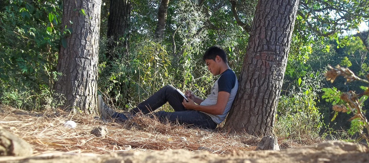 A man sat under a tree writing poetry
