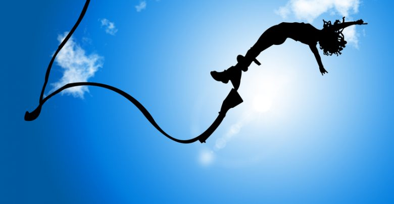 A bungee jumper silhouetted against the sky