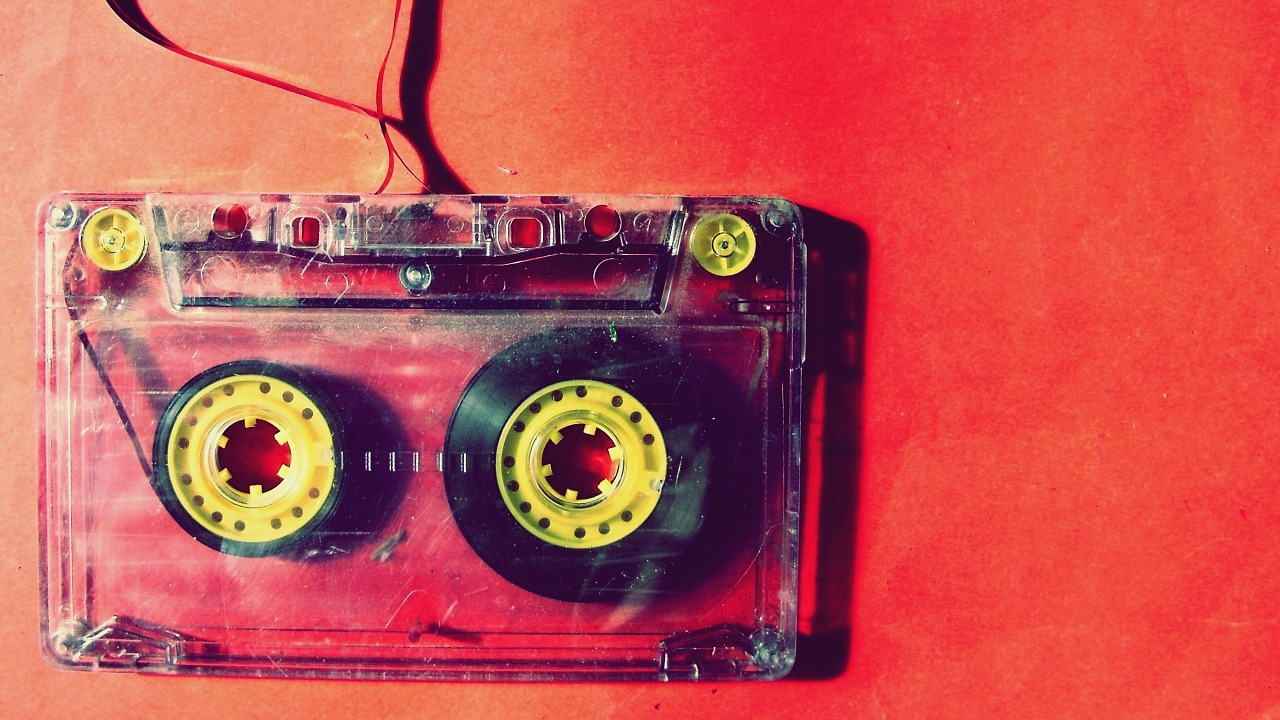 A cassette tape unwound on red background