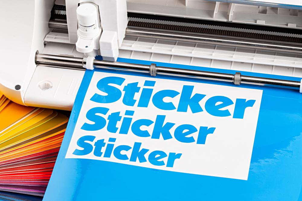 A Cricut machine cutting a vinyl sticker