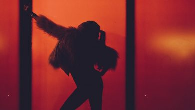 A silhouette of a woman wearing faux fur