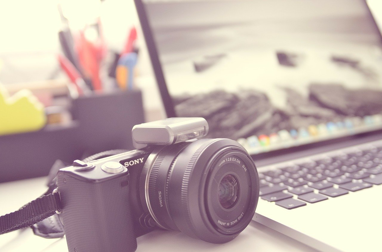 A camera next to a laptop