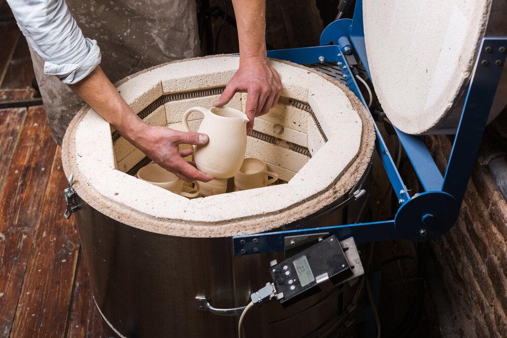A man using an electric kiln