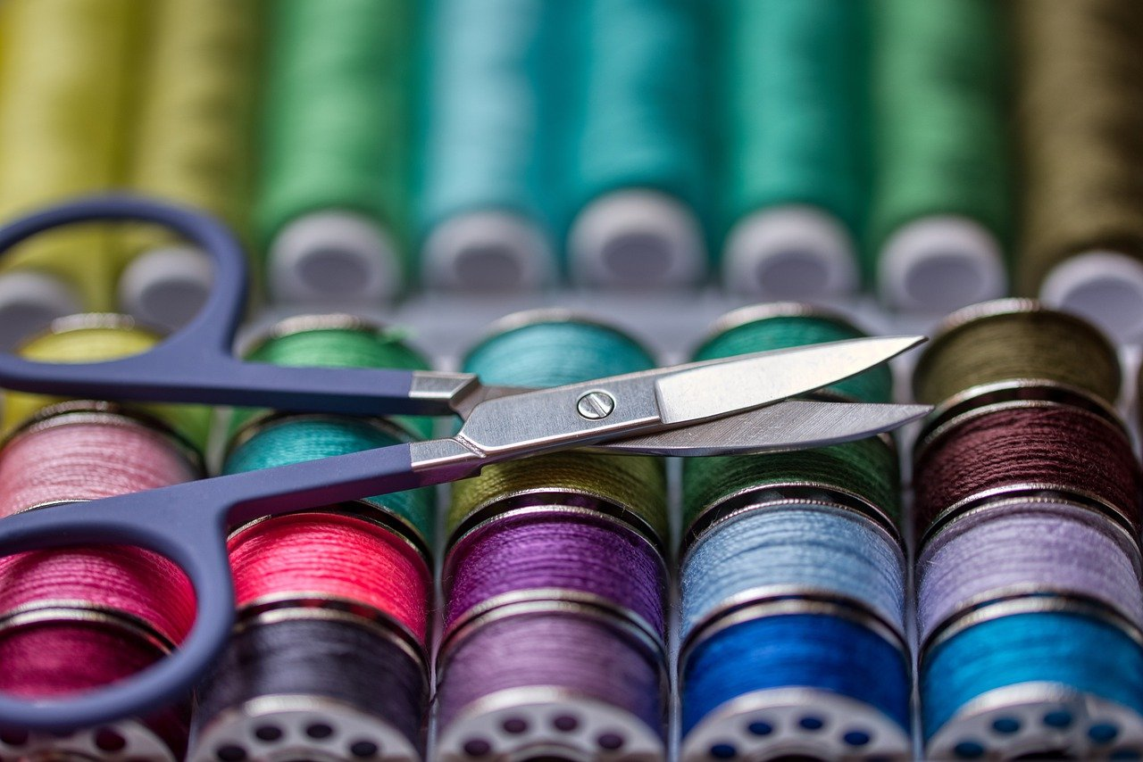 Different color sewing threads with scissors on top